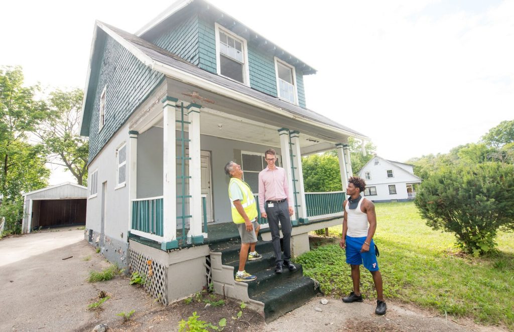 Flint's blight busters (from left to right) Raul Garcia Joel Arnold and DeAndre Price enjoy a lighter moment in front of one of the homes they helped to board-up. Photo: Paul Engstrom